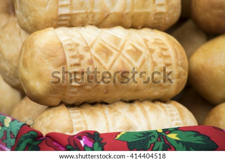 Oscypek laying on the traditional floral cloth. Traditional smoked sheep milk cheese made in Poland - stock photo
