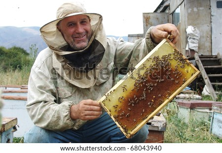 OSH, KYRGYZSTAN - JULY 13: Man shows off his honeycomb on July 13, 2009 in Osh, Kyrgyzstan. NGOs are training local people in beekeeping to supplement their incomes.