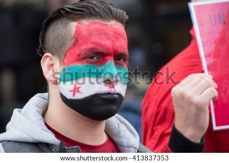 OSLO - MAY 1: A refugee with Syrian flag face paint protests during the May Day parade in Oslo, Norway, May 1, 2016.