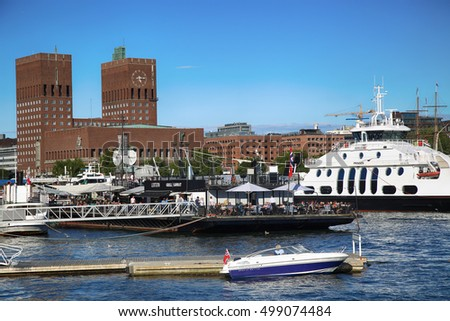 OSLO, NORWAY AUGUST 17, 2016: People walking on modern district on street Stranden, Aker Brygge district and in the background is the City Hall in Oslo, Norway on August 17,2016.