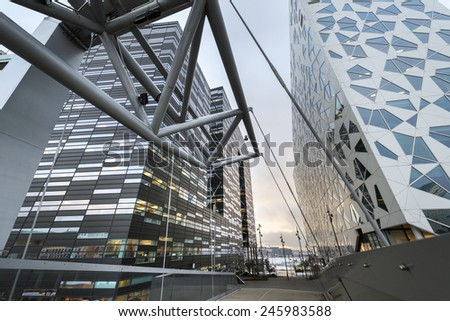 OSLO, NORWAY - DECEMBER 31, 2014: New apartment blocks and a walkway leading to the 'Barcode buildings' redevelopment on former dock and industrial land in central Oslo, Norway. - stock photo