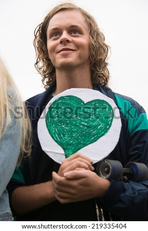 OSLO - SEPTEMBER 21: A young man carries a green heart as thousands march through downtown Oslo, Norway, to support action on global climate change, September 21, 2014. - stock photo
