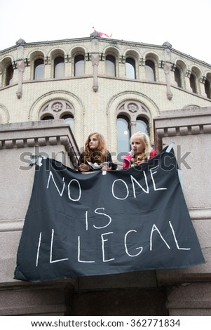 "OSLO - SEPTEMBER 12: Norwegians rallying in support of Syrian refugees hold a banner reading, ""No One Is Illegal"", in front of the parliament building in Oslo, Norway, September 12, 2015. - stock photo"