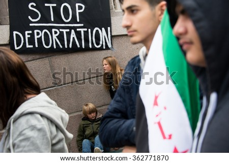 "OSLO - SEPTEMBER 12: Young men hold a Syrian flag near a banner reading, ""Stop Deportation"", at a rally supporting Syrian refugees at the parliament building in Oslo, Norway, September 12, 2015. - stock photo"