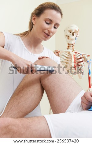 Osteopath Giving Ultrasound Treatment To Male Client With Sports Injury - stock photo