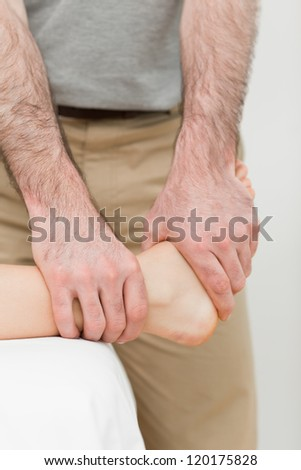 Osteopath manipulating the ankle of a patient in a room - stock photo