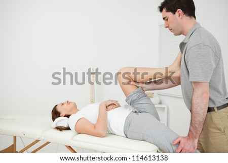 Osteopath stretching the leg of his patient in his medical room - stock photo