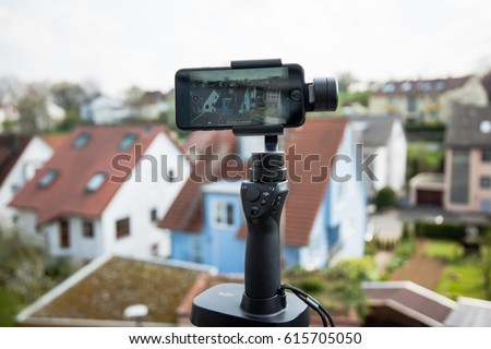 Ostfildern, Germany - April 5, 2017: A DJI Osmo Mobile with stand is in action filming a panoramic timelapse video using an iPhone 7 smartphone. The DJI Osmo hardware and mobile app allows for smooth