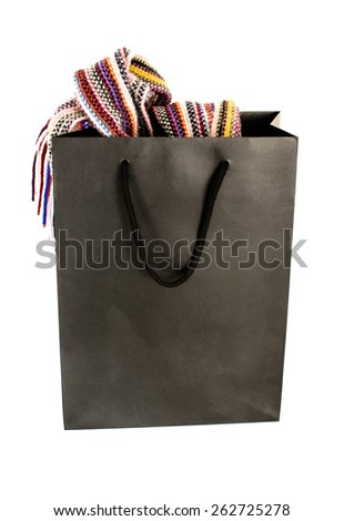OSTFILDERN, GERMANY - MARCH 14, 2015: A black paper shopping bag with a colourful scarf hanging out of it with shadow and reflection on a white background on March 14, 2015 in Ostfildern, Germany - stock photo