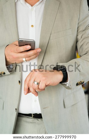 OSTFILDERN, GERMANY - MAY 14, 2015: A businessman is checking his Apple Watch while using his iPhone 6. The Apple Watch is the latest device by computer and smartphone manufacturer Apple Computer and - stock photo