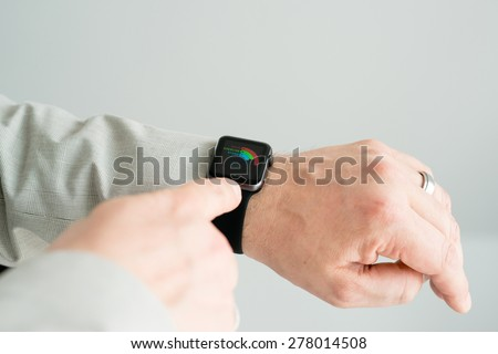 OSTFILDERN, GERMANY - MAY 14, 2015: A businessman is checking his daily activity rate using his black Apple Watch Sport. The Apple Watch is the latest device by computer and smartphone manufacturer - stock photo
