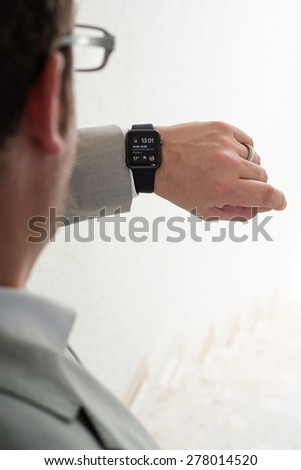 OSTFILDERN, GERMANY - MAY 14, 2015: A businessman is checking the time using his black Apple Watch Sport upon leaving his flat for work. The Apple Watch is the latest device by computer and smartphone - stock photo