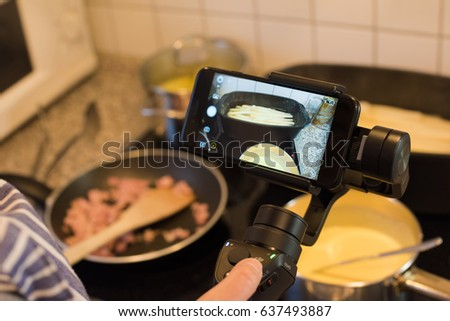 Ostfildern, Germany - May 7, 2017: A female blogger is producing a video while cooking asparagus with potatoes, ham and hollandaise sauce using the DJI Osmo Mobile steadycam gimbal and an Apple iPhone