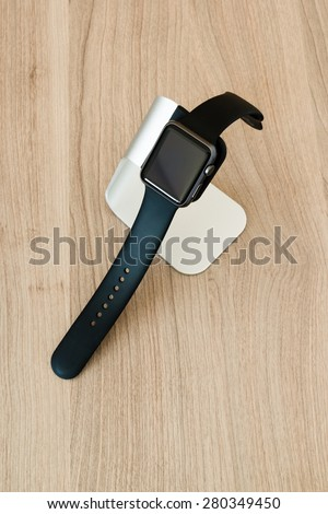 OSTFILDERN, GERMANY - MAY 21, 2015: An Apple Watch Sport 42mm with space gray aluminium case and black sport band in a stylish stand by manufacturer Spigen on a wooden table. The Apple Watch is the - stock photo