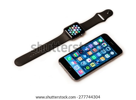 OSTFILDERN, GERMANY - MAY 13, 2015: The new Apple Watch, a black 42mm Apple Watch Sport displaying the apps screen next to the iPhone 6 displaying the home screen. The Apple Watch is the latest device - stock photo
