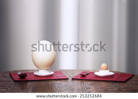 Ostrich and hen eggs in  ceramic egg-holders, two spoons on a wooden table - stock photo