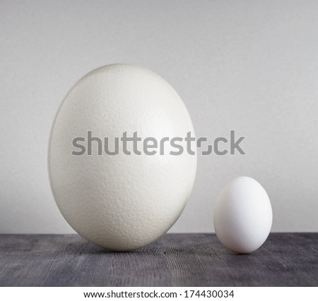 Ostrich egg and chicken egg on black table. - stock photo