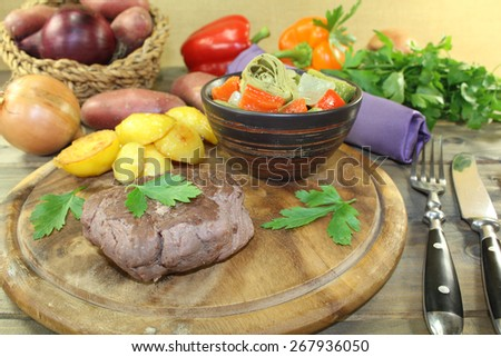 Ostrich steak with crispy baked potatoes and parsley on a wooden board