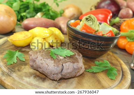 Ostrich steak with crispy baked potatoes and vegetables on a wooden board