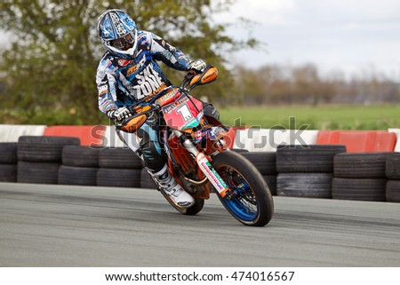 OSWESTRY, UK - APRIL 27: An unnamed rider competing in the NoraSport UK Supermoto championship accelerates into a right hand corner at the Rednal race circuit on April 27, 2013 in Oswestry