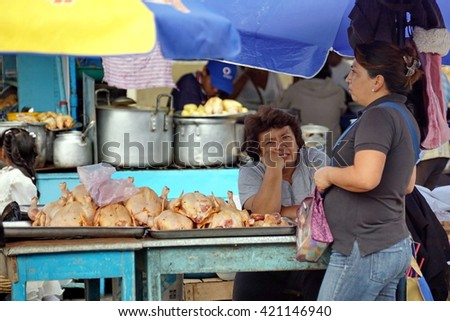 OTAVALO, ECUADOR - CIRCA FEBRUARY 2013: Women at a chicken stand in the Otavalo Market