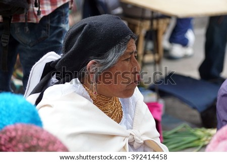 OTAVALO, ECUADOR - FEBRUARY 13, 2016: Indigenous woman in traditional dress in the market, turned sideways - stock photo