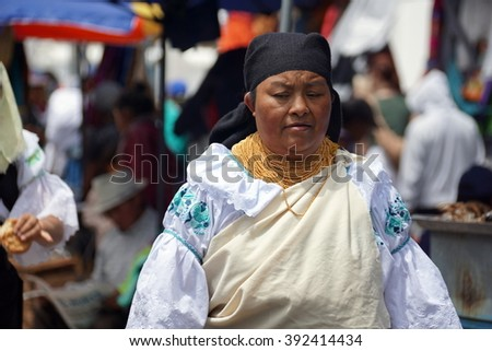 OTAVALO, ECUADOR - FEBRUARY 13, 2016: Indigenous woman in traditional dress walking through the market