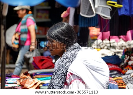 OTAVALO, ECUADOR - FEBRUARY 13, 2016: Woman in traditional dress walking down an aisle with a baby on her back in the market