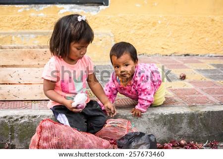 OTAVALO, ECUADOR - JAN 3, 2015: Unidentified Ecuadorian children with onion at the Otavalo Market. 71,9% of Ecuadorian people belong to the Mestizo ethnic group - stock photo