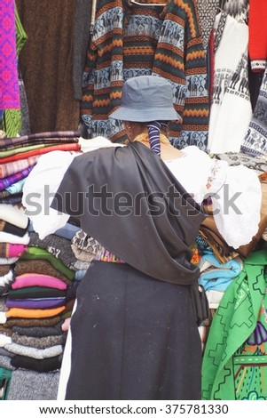 OTAVALO, ECUADOR - JANUARY 9, 2016: Quechua woman in traditional dress works at a clothing stall in the market