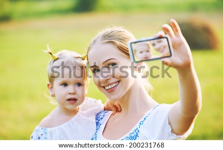 other and baby daughter photographing selfie themselves by mobile phone in summer - stock photo