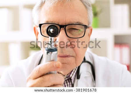 Otolaryngologist specialist looking through otoscope - stock photo