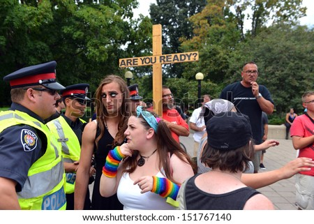 OTTAWA - AUG 25:  Gay Pride participants talk to police as a Christian preaches against homosexuality after the crowd decides to stop listenting at the annual Gay Pride Parade Aug 25, 2013 in Ottawa - stock photo