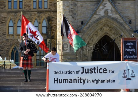 OTTAWA, CANADA - APR 12, 2015: Bagpiper plays Amazing Grace as tribute at protest Ottawa to bring attention to the plight of the Hazara peoples and the hostages being held in Afghanistan. - stock photo