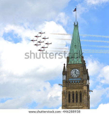 OTTAWA, CANADA - JUL 1 2016:  Canadian Air Demonstration Squadron, known as the Snowbirds fly by the Peace Tower as part of the Canada Day celebration on Parliament Hill. - stock photo