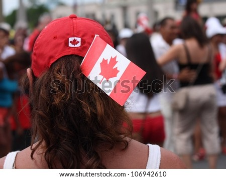OTTAWA, CANADA - JULY 1: A woman watching others dance in the street on Canada Day, July 1, 2012 in Ottawa, Ontario. Canada Day is a national holiday, and is celebrated each July 1st.