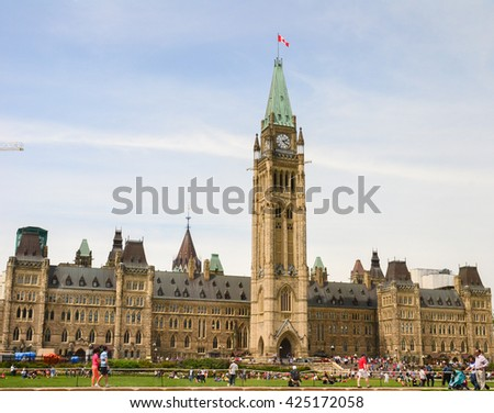 Ottawa, Canada - May 21, 2016: Parliament Hill in Canadian capital Ottawa a day before Queen Victoria day with many tourists walking around. - stock photo
