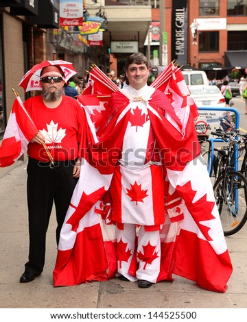 OTTAWA - JULY 1:  Unidentified revelers display their Canadian patriotism amongst the huge crowd in town for the annual Canada Day celebration July 1, 2013 in the Canadian capital of Ottawa. - stock photo