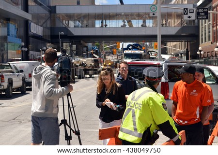 OTTAWA - JUN 10, 2016: CTV reporter Leah Larocque on Rideau street that was closed due the sinkhole that opened up two days before to interview City Councillor Mathieu Fleury, Center. - stock photo
