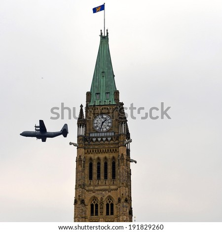 OTTAWA - MAY 9:  An aircraft used by the Canadian Forces in Afghanistan does a fly by the Peace Tower during national Day of Honour for veterans May 9, 2014 in Ottawa, Canada - stock photo