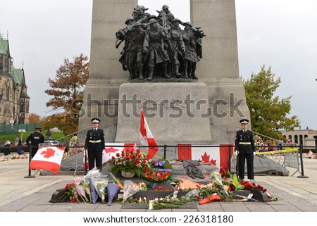 OTTAWA - OCT 25, 2014:  Sentries stand at attention while mourners pay respect at the Ottawa Cenotaph where guard Nathan Cirillo was shot 3 days before.  An armed policeman, left, is also on site. - stock photo