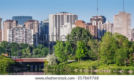 Ottawa River and capitol city skyline along the parkway - late springtime afternoon - early evening approaches.  Tall buildings, apartments and condominiums comprise an Ottawa city skyline. - stock photo