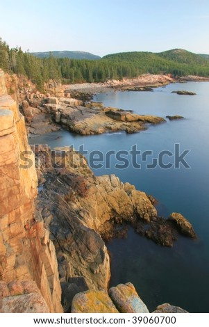 Otter Cliffs and calm shoreline illuminated by the early morning sun in Acadia National Park, Maine