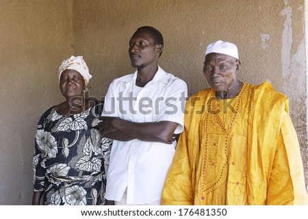 OUAGADOUGOU, BURKINA FASO - NOVEMBER 16: portrait of a son to his parents home in front of their house in Ouagadougou, november 11, 2010 - stock photo