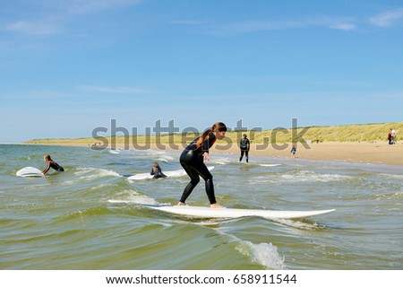 Ouddorp, Netherlands- june 11, 2017: Family fun on the beach. Learning to surf on the waves.