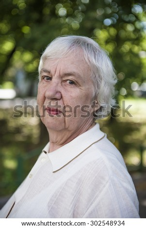 Ouedoor portrait of a gray-haired elderly woman - stock photo