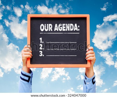 Our Agenda on blackboard with hands are holding.   - stock photo