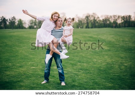 Our father is the best! Strong young father lifting his wife and daughter at the grass field outdoors - stock photo