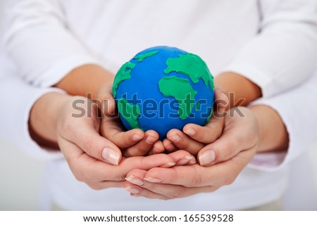 Our legacy to the next generations - a clean environment, with child and adult hands holding earth globe - stock photo
