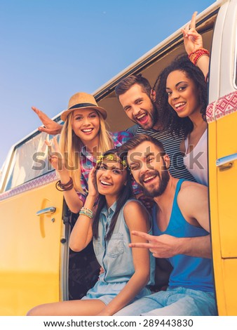 Our lives are full and happy. Group of happy young people smiling at camera and gesturing while sitting inside of retro mini van - stock photo